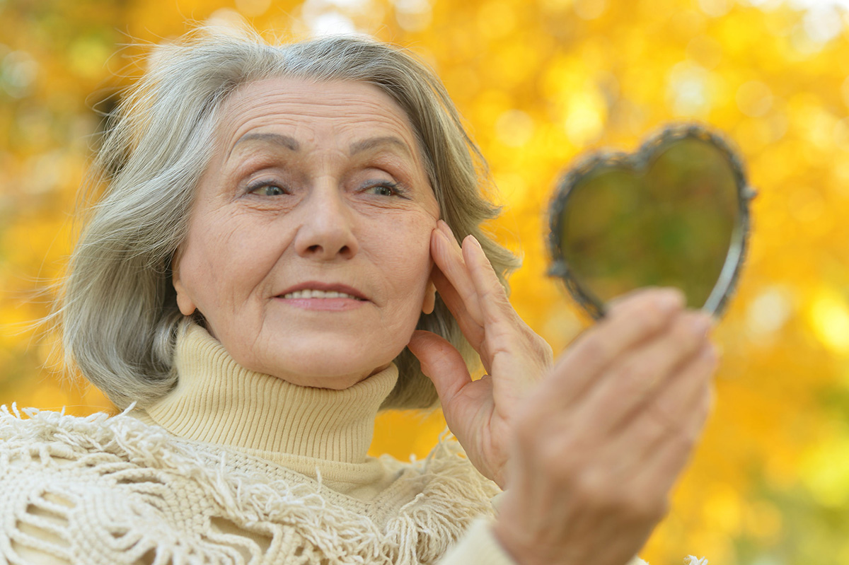 Portrait of a elderly woman with mirror in autumn